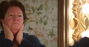 Marcia Whitehead as Compline in the bathroom mirror